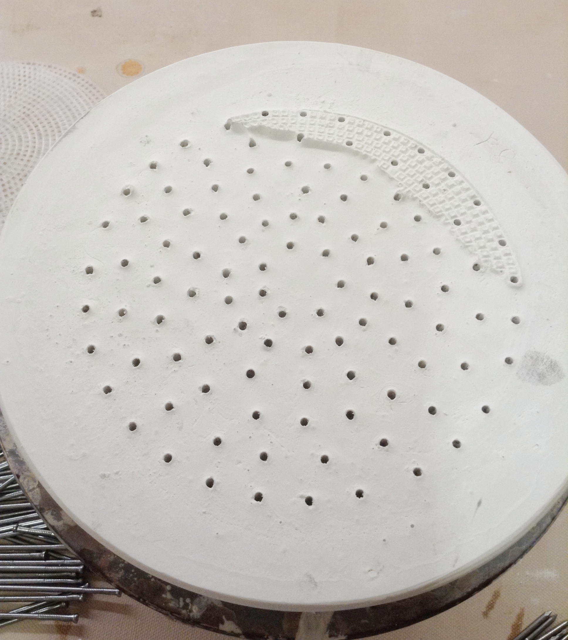 Round array made of plaster. Holes are about 1/2 inch deep to accept rod material.