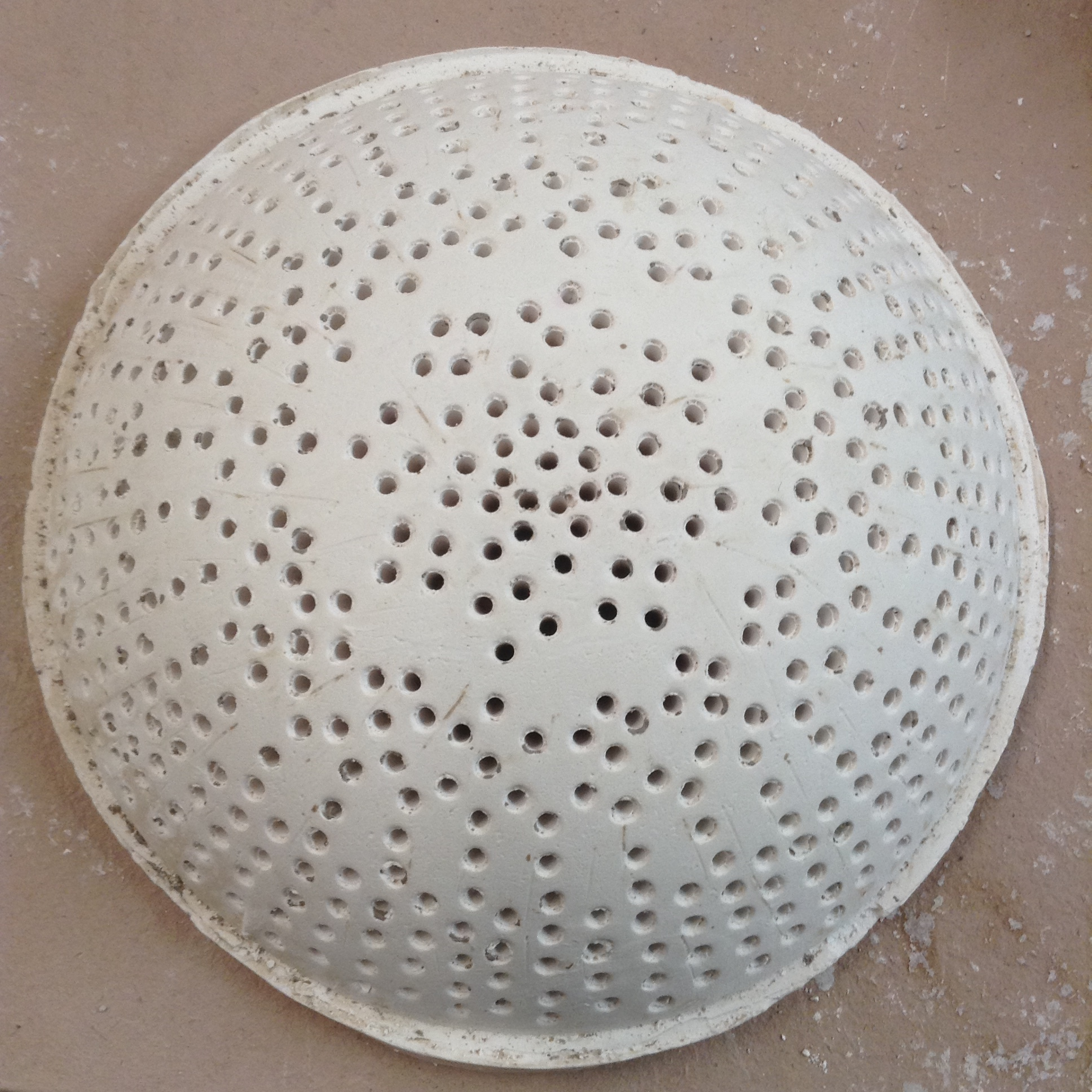 Large plaster dome form with different hole spacing in different areas.