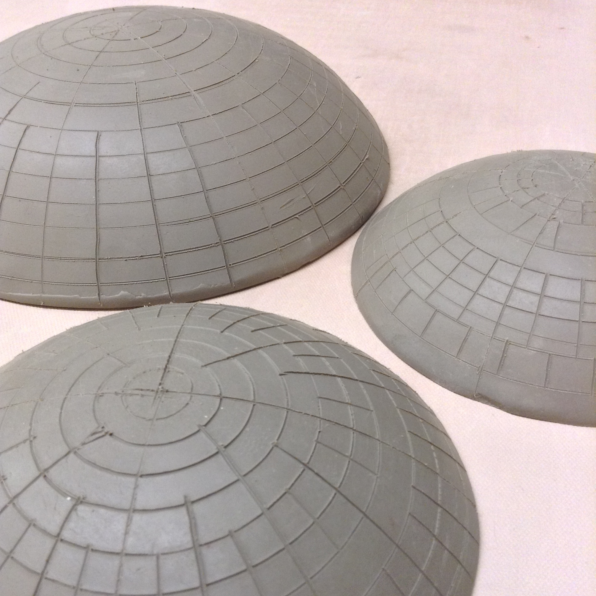 Several clay dome shapes with lines drawn on outside to indicate to me where to drill the holes. Unclear yet whether these subtle changes will matter after all is finished. But I could always make these as just normal ceramic bowls!