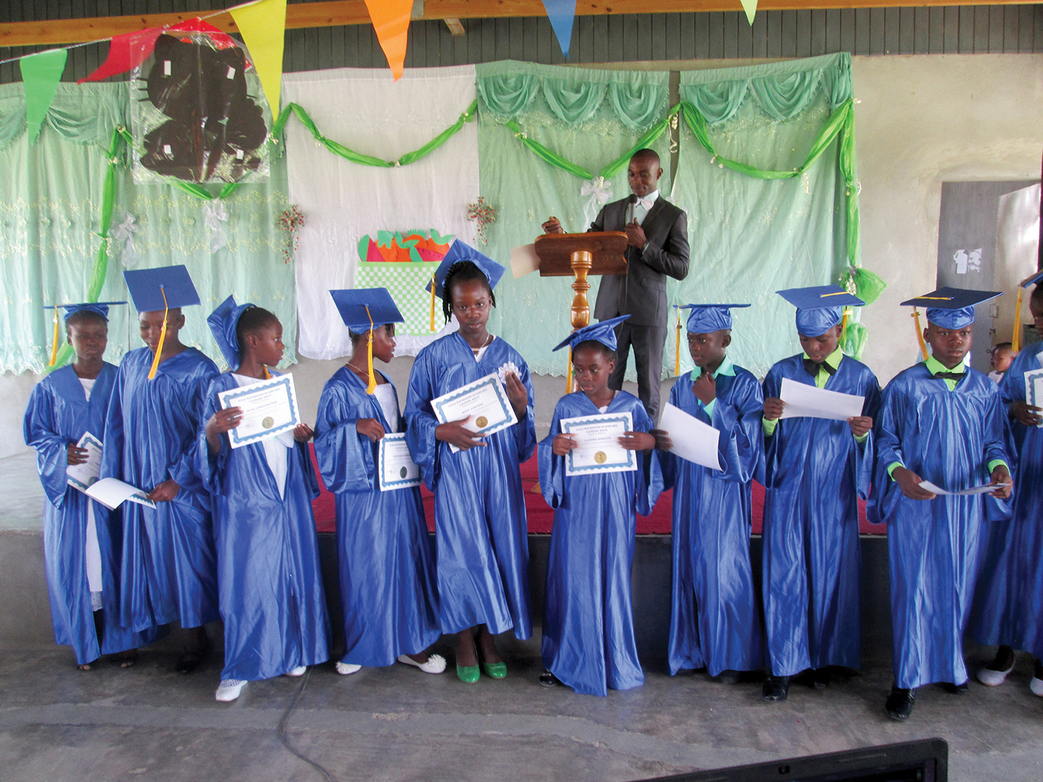 Pastor Yaguel, graduate from the class of 2005, celebrates sixth graders reaching the milestone of graduating primary school in Haiti.