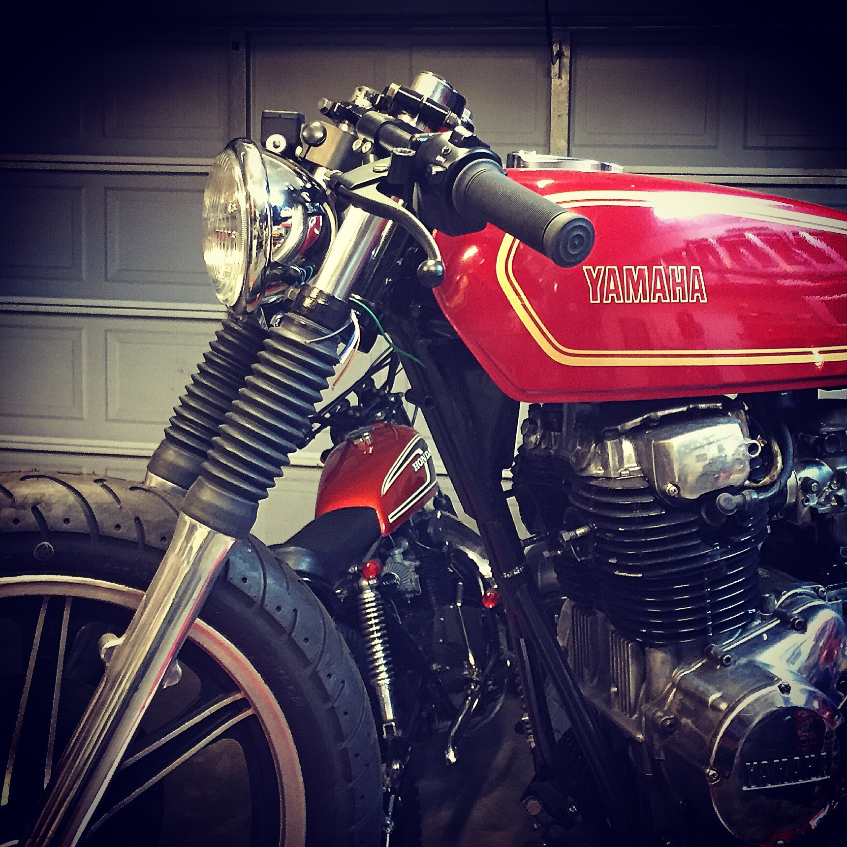 We had an old Honda SL350 headlight bucket laying around. On a whim I set it between the forks and fell in love with how it looked. With custom bracket we were able to tuck it in with a bottom mount. It instantly made the bike look mean!