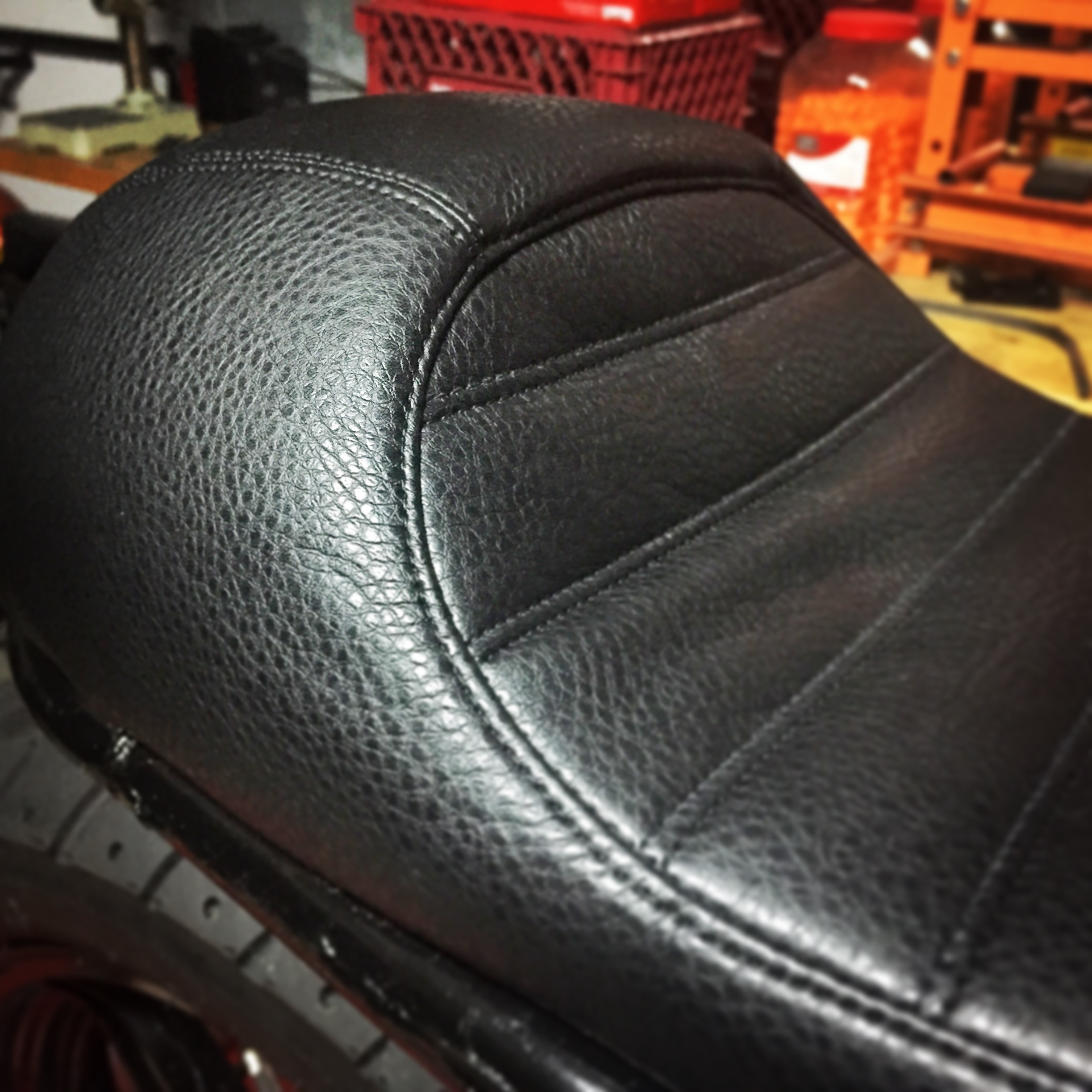 We hand craft all of our seats in house. We decided to go with an upholstered café bump on this bike. The seat turned out beautiful, but we would later decide that the fork gaiters and stance of the bike demanded a brat style pancake seat. This cover would end up in the garbage.