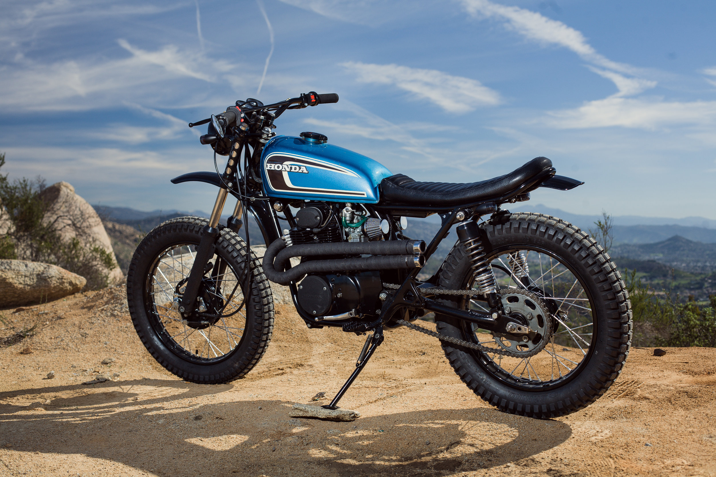 """This is the third SL350 we have built in this basic style. They were the premier off road bike of the day, and still perform pretty well with the vintage styling that we love. We have used the tank from a CB360 on all three builds. The seat pan, foam, upholstery is all custom and done in house. The front fender is from a CX500 but has been shortened by about 6"""". New chrome spokes and black powder coated wheels pair nicely. The headers are from a CL350 from the same era. Wrapped in DEI Titanium header wrap, they stay cool for your left leg while riding. Here are links to these products:    Header Wrap      Rear Tire      Front Tire"""