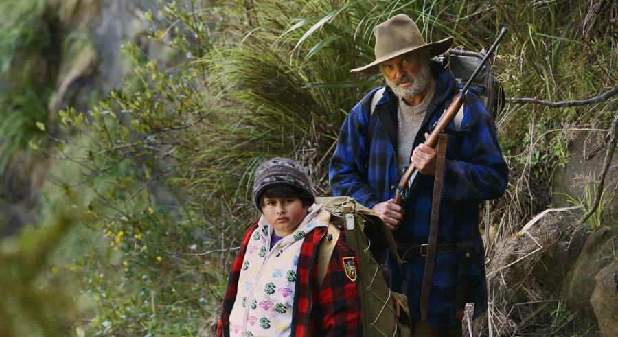 """This comedy drama, the most successful film ever produced in New Zealand, with director Taika Waititi, is based on Barry Crump's beautiful novel, """"Wild Pork and Watercress"""". Rebellious foster teenager, Ricky, is dumped at a remote shack with the loving Bella and husband Hector. Tragedy suddenly appears so Ricky and Hector, with their dogs, have to disappear into the bush, ahead of a man-hunt. This is a warm-hearted, yet consistently clever film."""