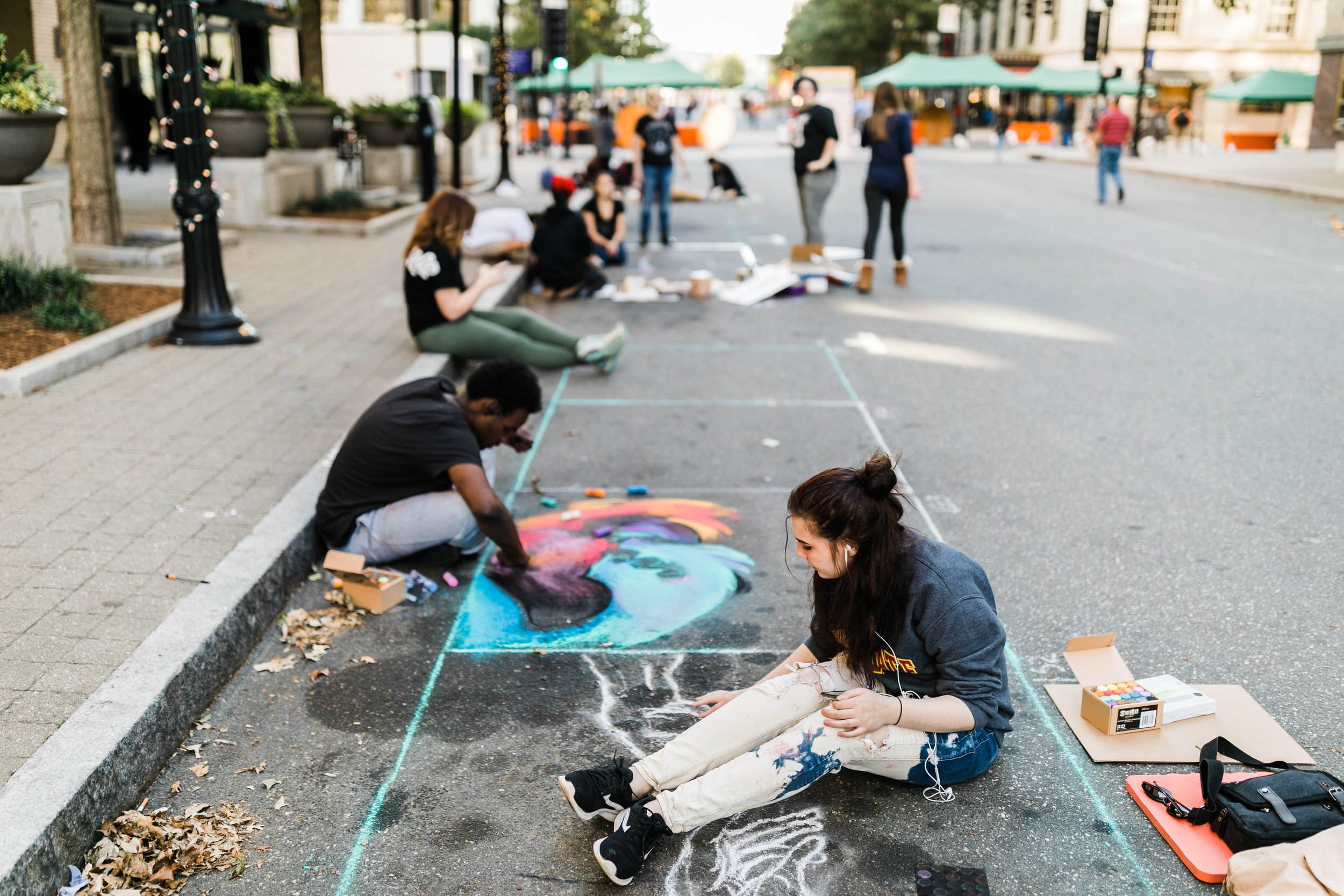 Two young adults painting with chalk on Fayetteville St.