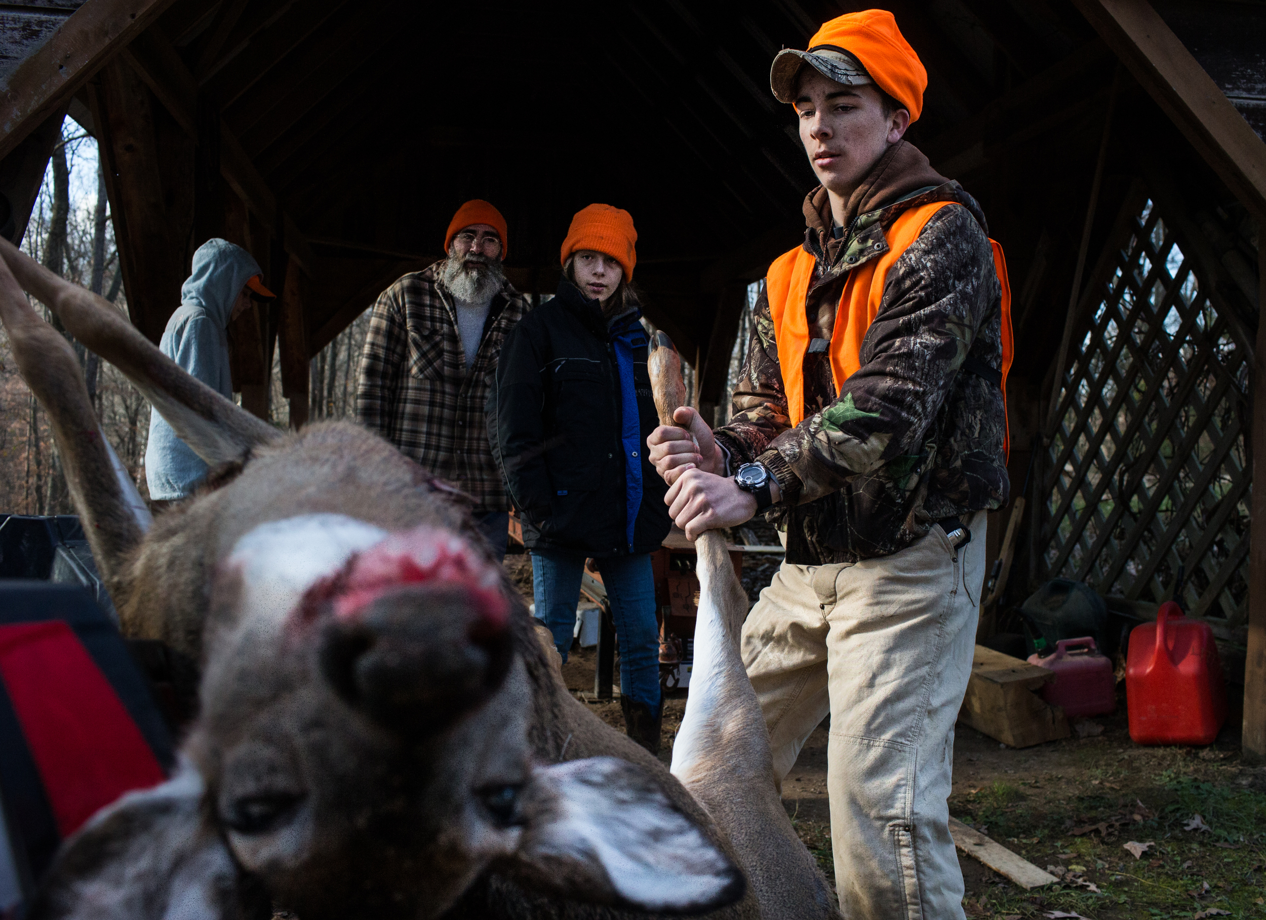After a long morning of hunting, Tyce Peters, 15, right, dragged a doe into his families shed so that his dad, Aaron Peters, could begin skinning and butchering the deer. The Peters, a family of 13, live in Richardsville, Kentucky, and enjoy hunting anything from deer to coyotes.