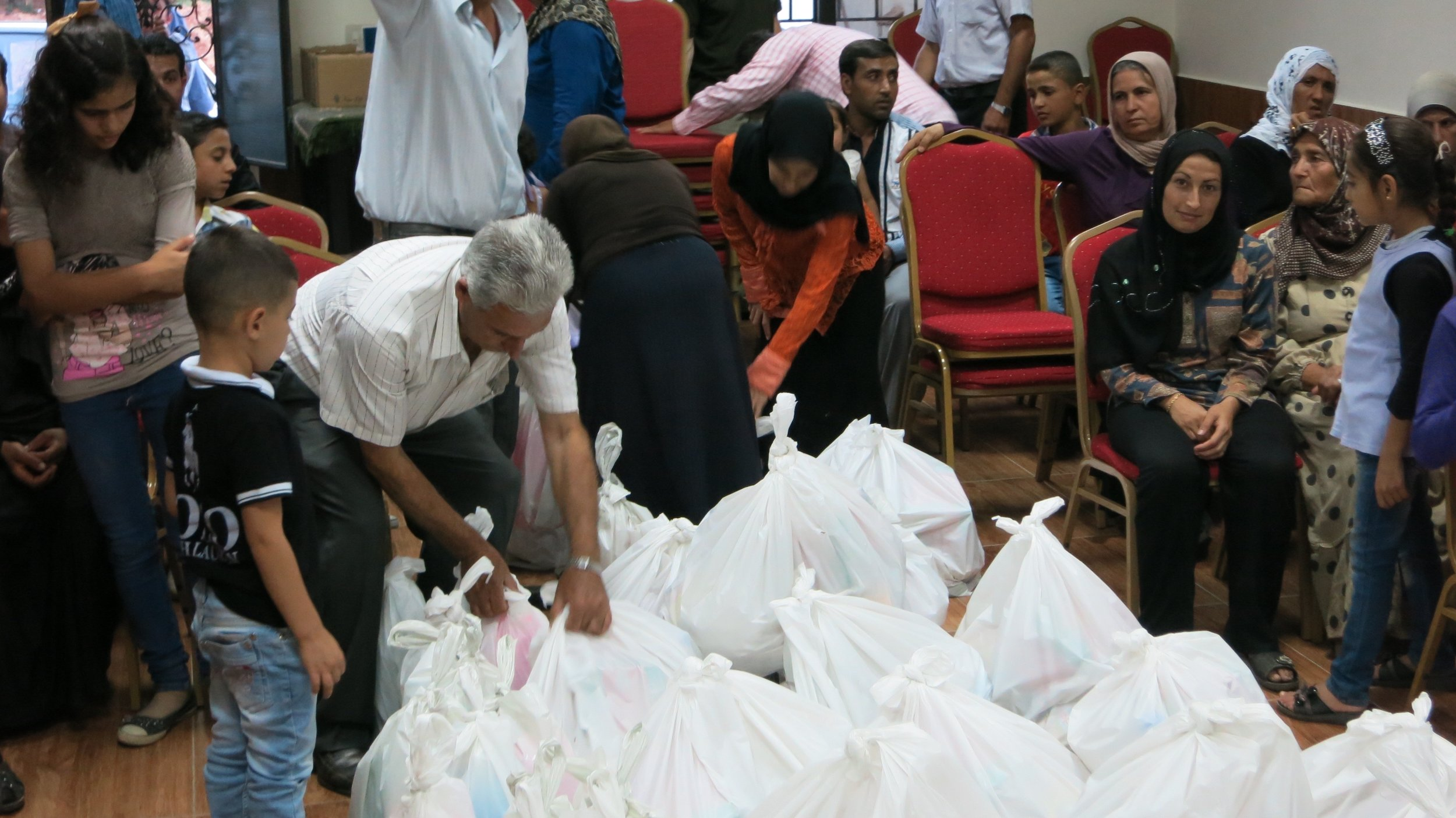 Refugees receive food and aid parcels from at the Call of Hope Center in Lebanon
