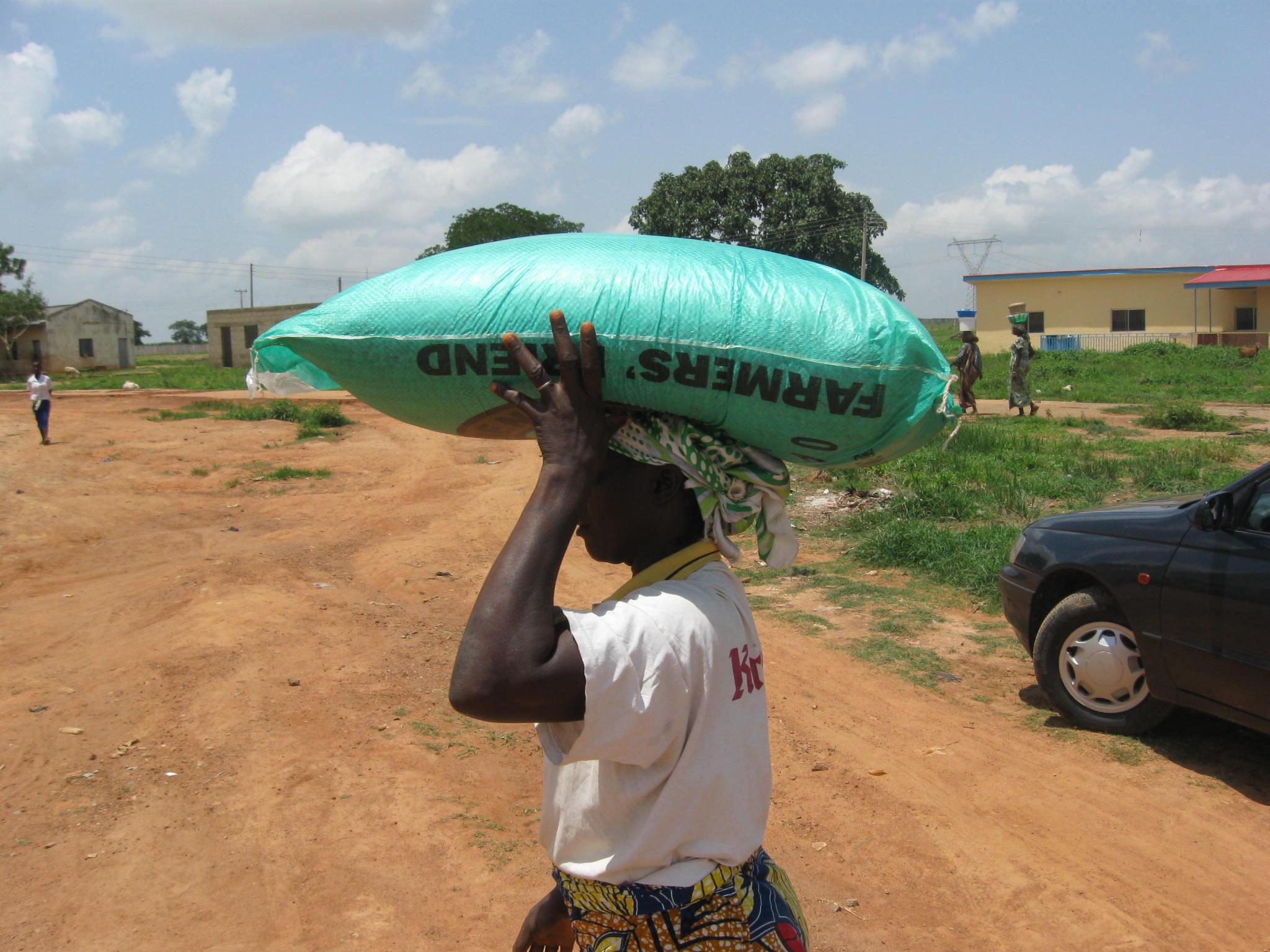Another+refugee+woman+walks+away+with+her+bag+of+fertilizer.JPG