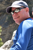 """Gordon is a founding member of Alpine Ascents and is responsible for overseeing all operations and creating written materials, researching climbing and cultural histories. He manages all aspects of the business, our office and is our marketing expert with a keen interest in client care and customer service. Details, details, details…  On the travel front, he is a long-time independent traveler, and scouts new locations such around the globe with a particular focus on the Indian subcontinent. Most recently Gordon lectured in and visited Kosovo and the Western Balkans; and the region of Ladakh, India researching new trekking areas. Over the last 30 years he has spent over 5 years in the India region, visiting states such as remote as the hill tribe region of Nagaland, with other intrepid journeys to Mongolia, Iran and Yemen. Gordon leads most of our India trips, such as treks or private journeys such as the art and architecture tour of Central India.  As a writer, he has had both fiction and travel works published in the U.S. and India. Gordon has served as an Indian subcontinent expert for numerous media sources such the New York Times, BBC and Outside Magazine and has appeared on CNN, MSNBC and the NBC Nightly News. Gordon and his family joined our trek to Everest base camp, introducing his kids to the joys of Asian travel. Any other """"spare"""" time Gord can be found coaching ice hockey in rinks of the Northwest and Canada."""