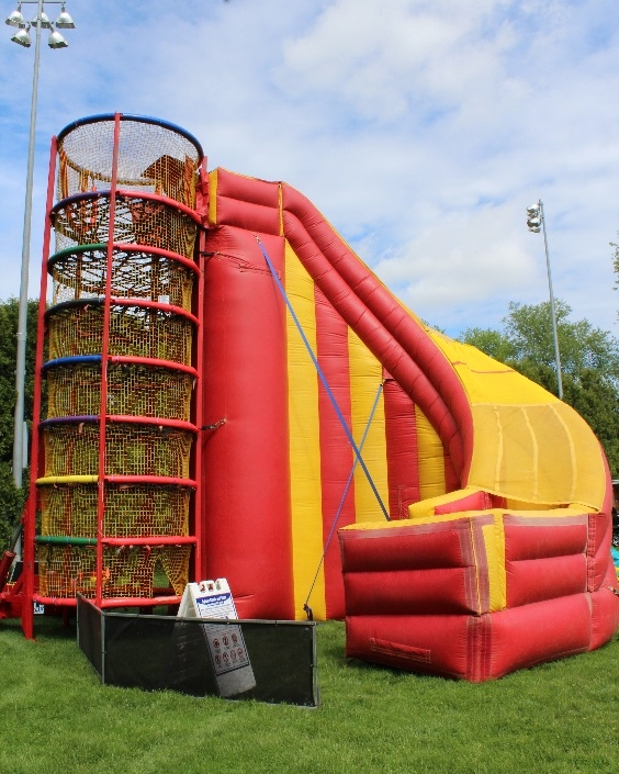 """Spider Mountain is the next level of climbing structures for your event! Your guests will find themselves weaving through the interior webbing of this 24' structure! Upon completing this exciting challenge, climbers then have the option of taking a thrilling plummet down our 40' inflatable slide or climbing and squirming back down through the webbing. Climbing through Spider Mountain, comprised of rubber strands enclosed in a soft polyester fabric, is deceivingly challenging and fun for all ages. All exposed hard surfaces are enclosed in four inch padding and the entire attraction is netted. It has been voted """"most fun and challenging attraction"""" on the exhibit floor at many different expositions. You can have up to 25 people inside the 24-foot-tall apparatus at once. There is no harnessing and therefore can maintain a very high throughput!   People Per Hour: 100+   Power Requirement: (3) 20 AMPS   Set-up Time: 2 Hours"""
