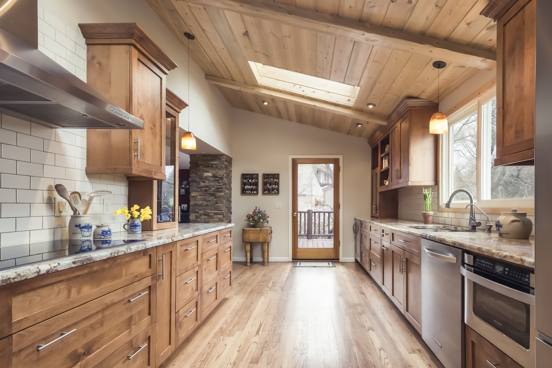 We exposed the shed roof on this galley kitchen and highlighted it with beetle kill pine planks.