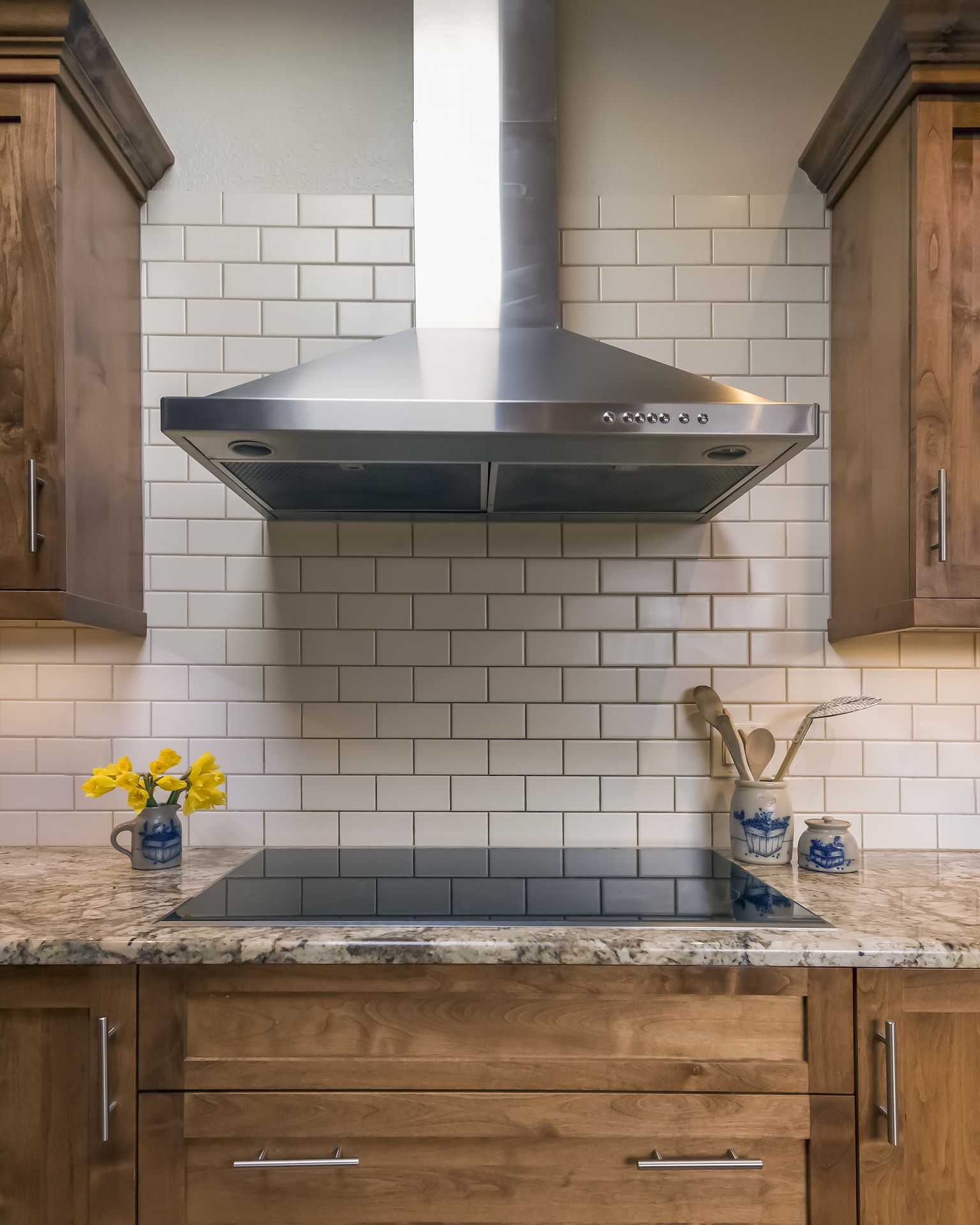 Simple, cream subway tile, a sleek induction stove and stainless steel hood create a simple backdrop for all the different wood species in the kitchen.