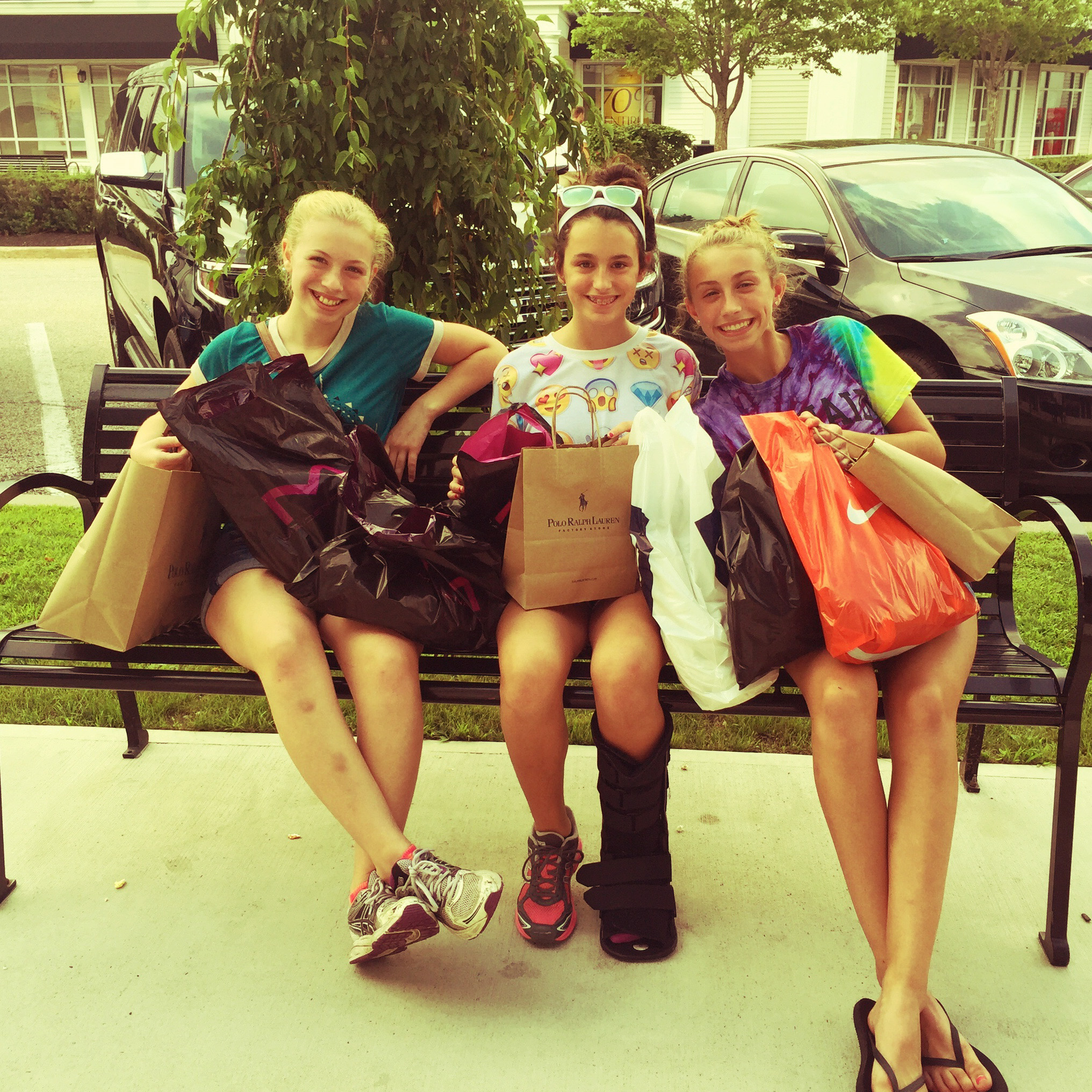 Three teenage girls sitting on a park bench with all of their shopping bags and new purchases prominently displaying brands such as Ralph Lauren and Nike.