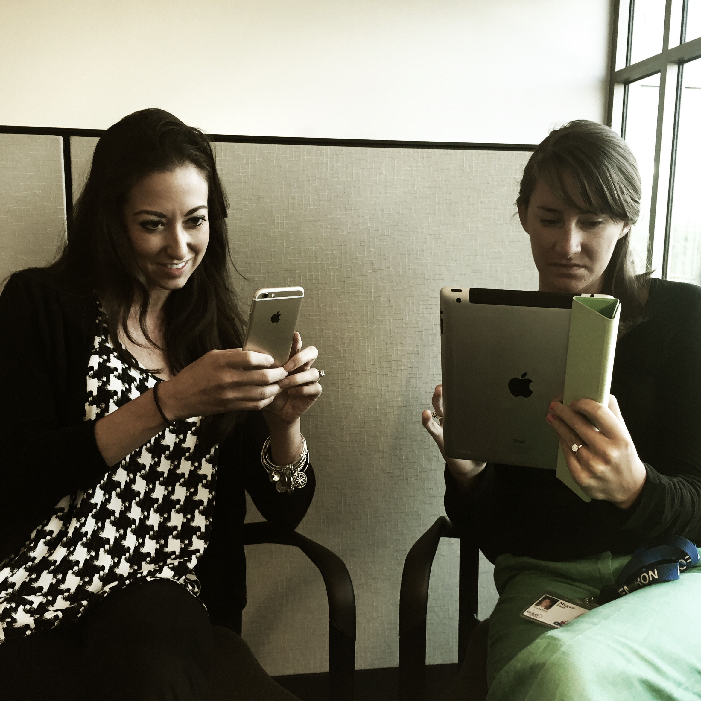 Two SparkShoppe marketing employees browsing online. Woman on the left using an Apple iPhone, woman on the right using an Apple iPad.