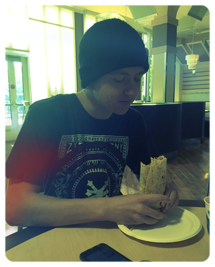 Young man sitting down eating a Taco