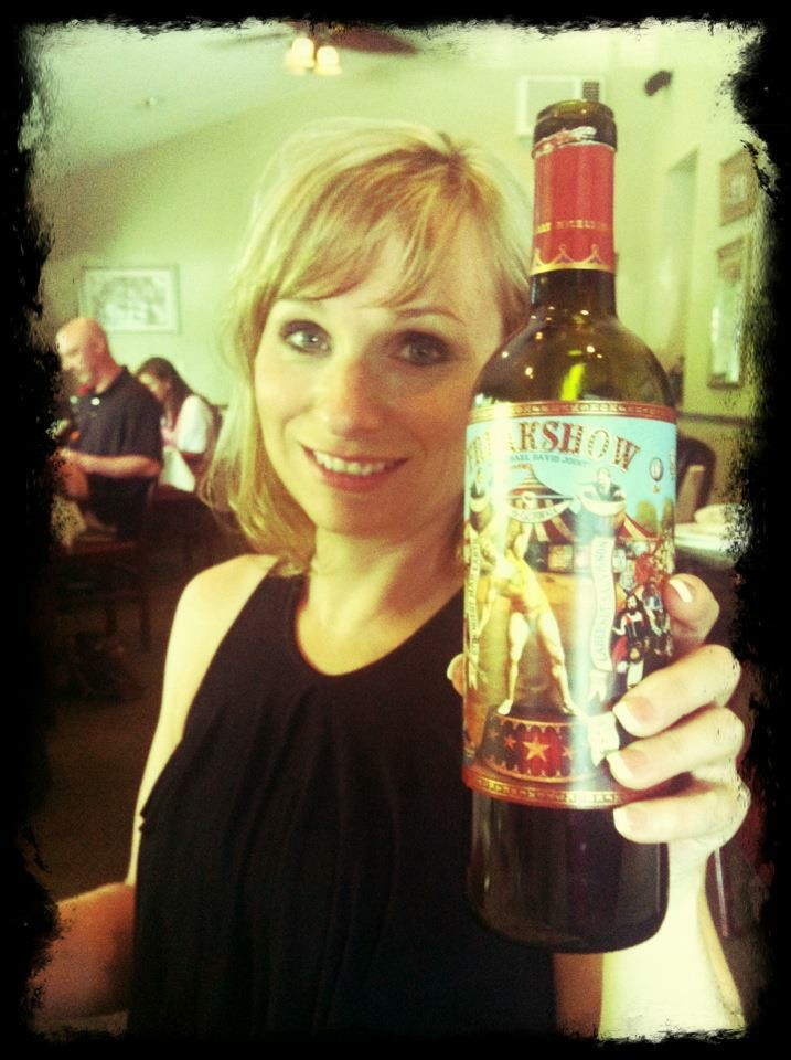 """SparkShoppe! marketing firm, Heidi Reale, displaying a bottle of """"Freakshow"""" red wine."""