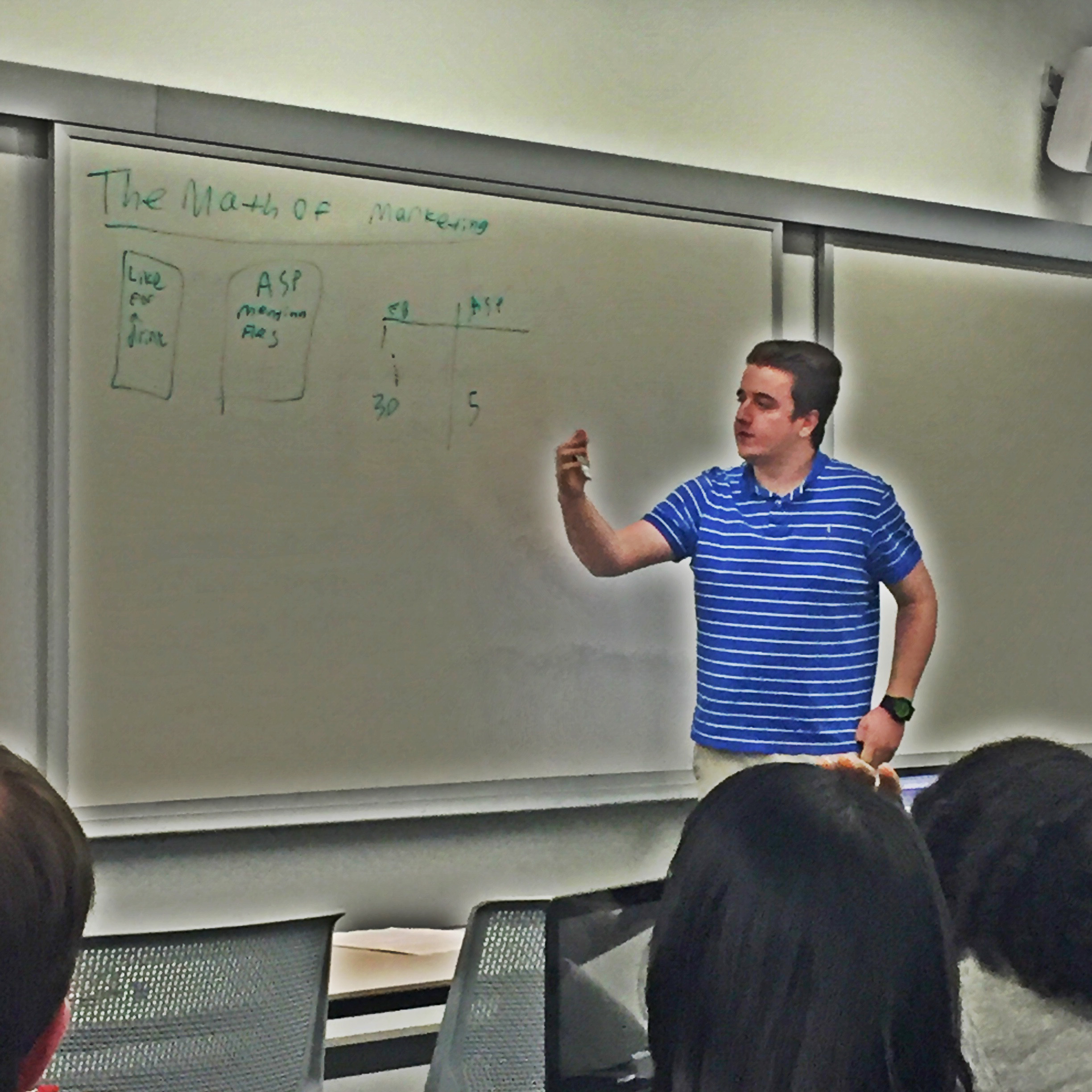 Ualbany student discussing the math of marketing with classmates in front of whiteboard with marketing formulas