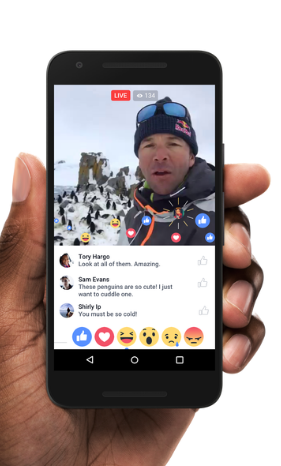 Image from Facebook Newsroom, Screenshot of a live video broadcasted by a man in a cold area who is surrounded by penguins. Comments and reactions are appearing.