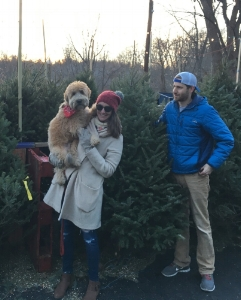 Senior Marketing Strategist, Megan Finin and her husband picking out a Christmas tree. Megan is holding her dog, Dublin a Wheaten Terrier.