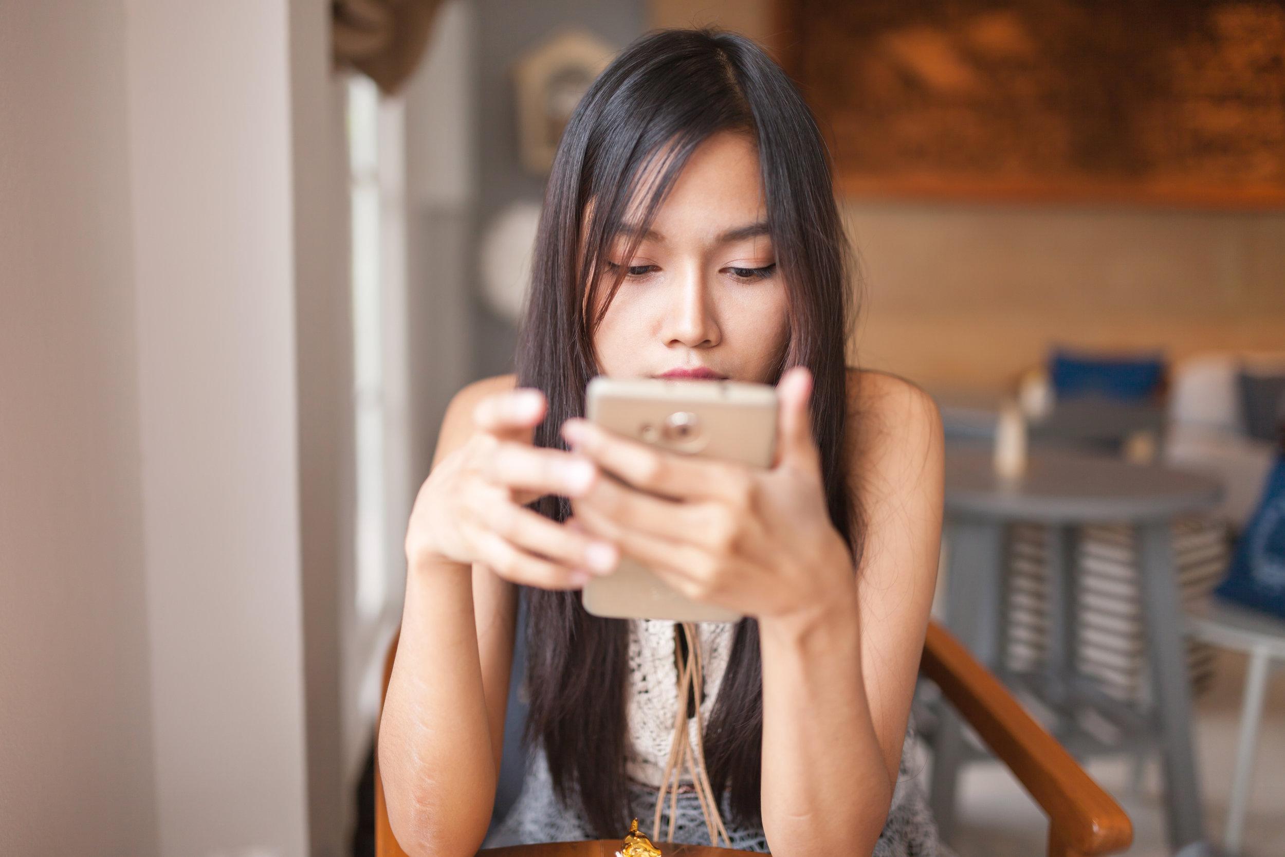 Girl browsing social media on her mobile device