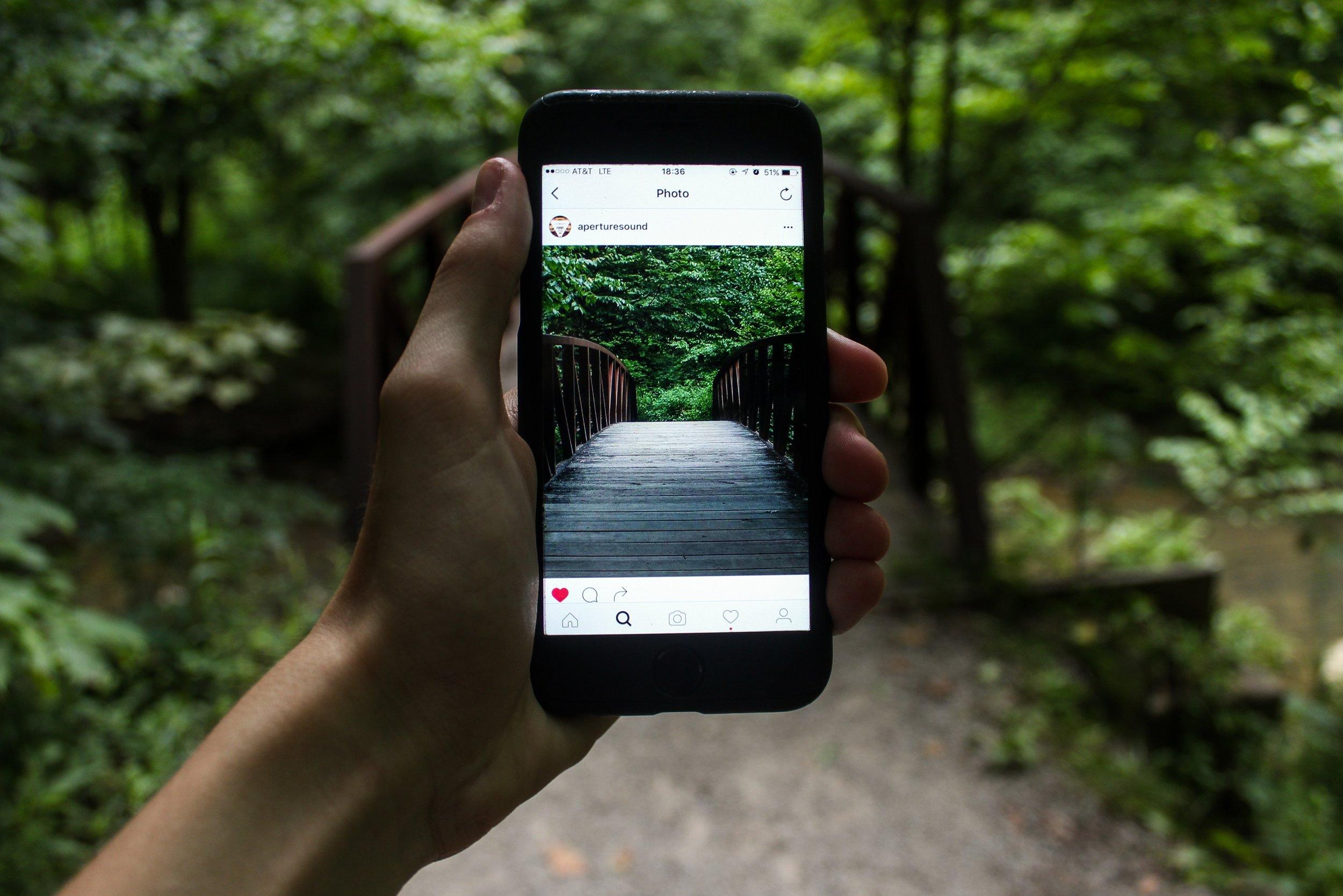 Instagram photo of bridge being held up in front of the actual bridge