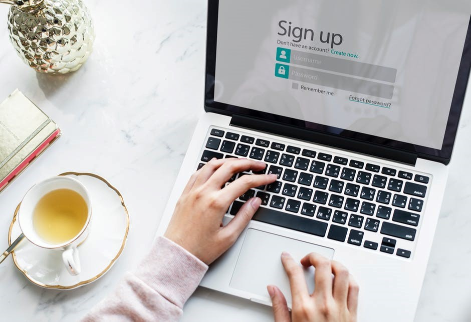 Woman signing up for an online account on her computer with a cup of tea next to her.