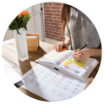 Woman creating a content calendar on a desk with a notebook and calendar.