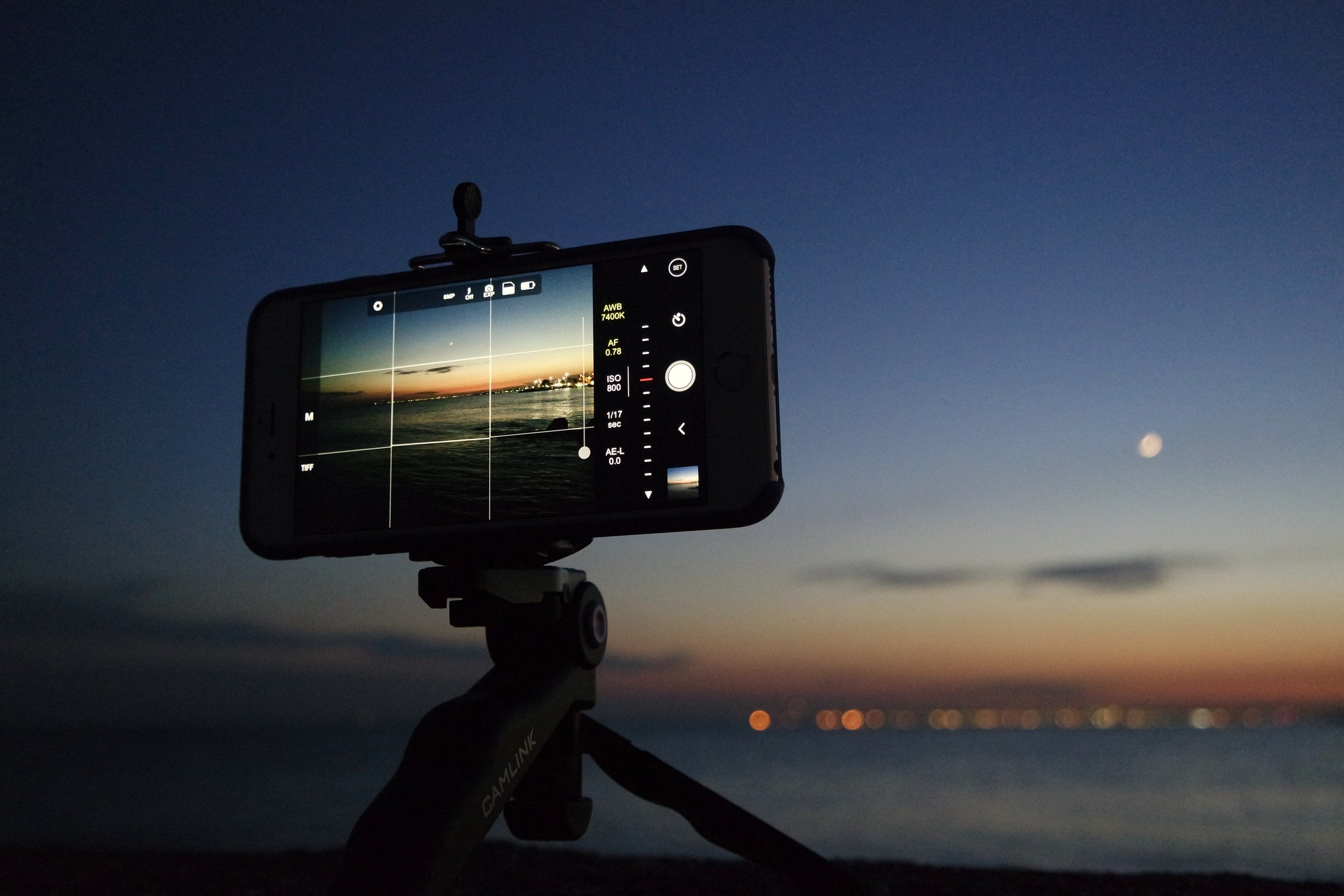 Smartphone on tripod recording a waterfront sunset scene for a video marketing campaign.