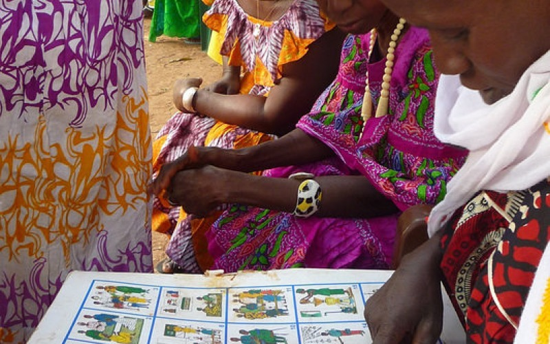 A group of women reviewing the human rights images that are the basis of Tostan's Community Empowerment Program. [Credit: Tostan}