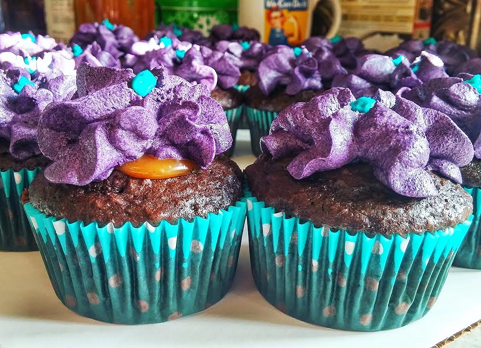 dark chocolate cupcake filled with salted caramel and topped with deep purple and turquoise buttercream flowers