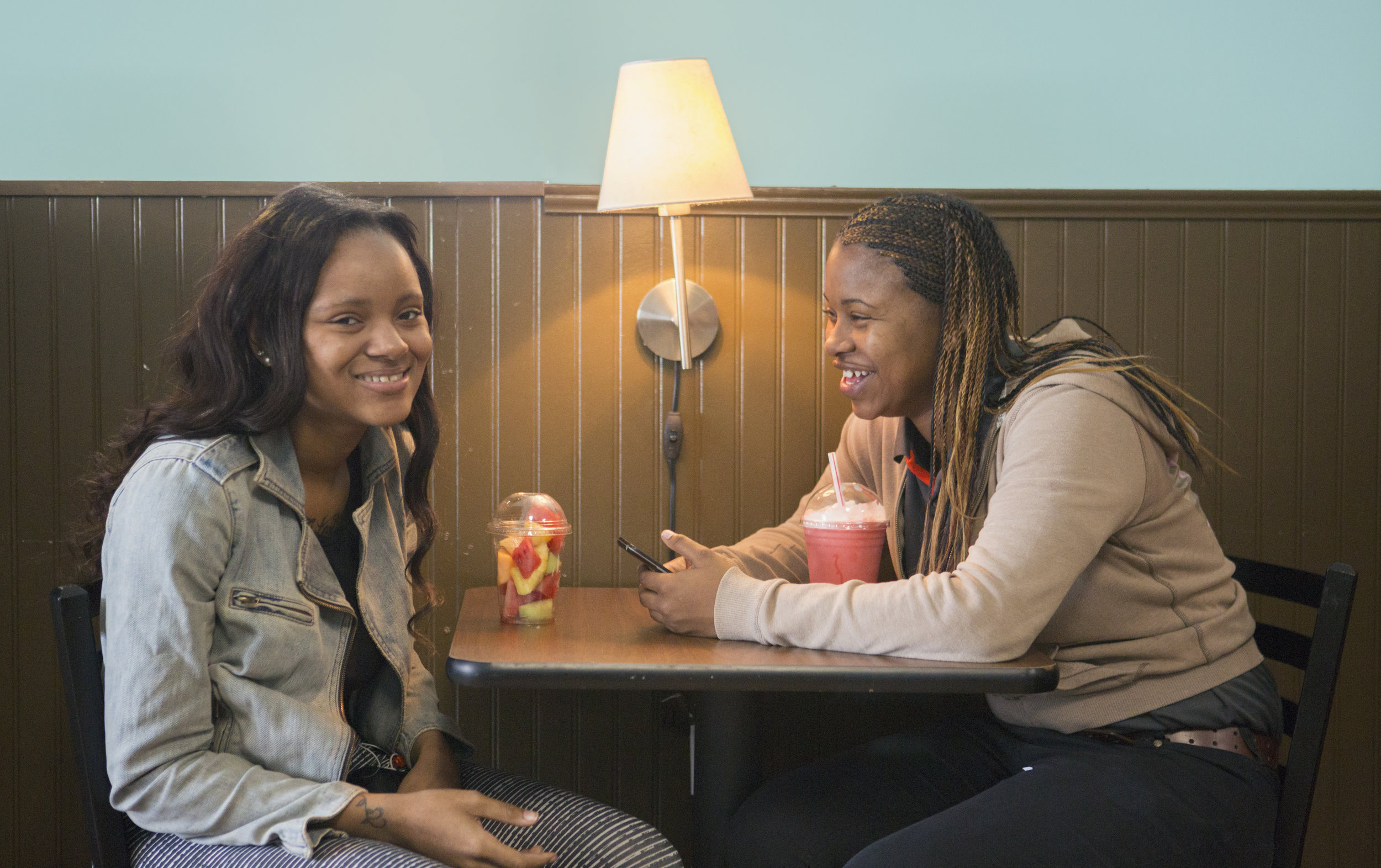Two young ladies enjoy conversation over food and drink at Community Grounds.