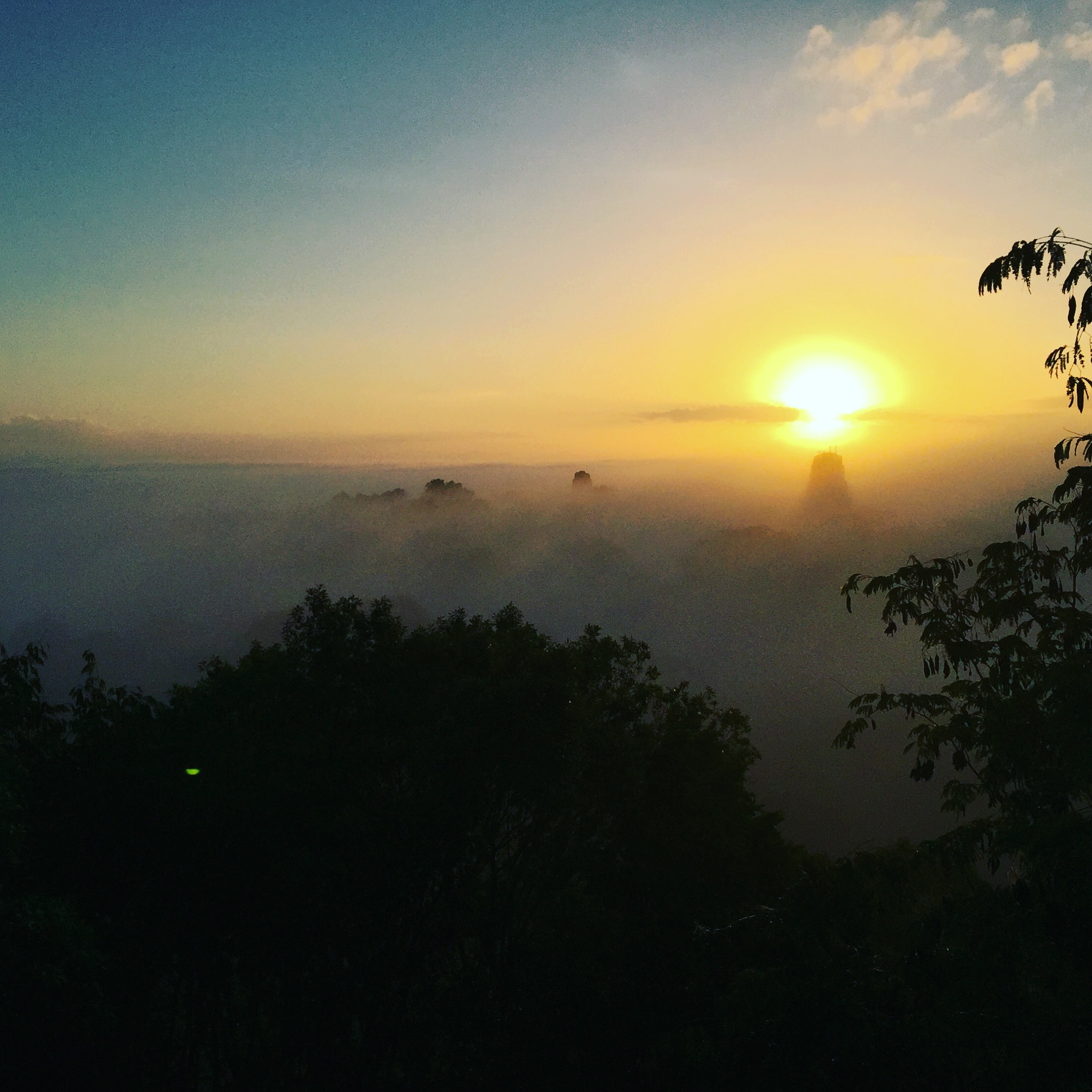 Sunrise from on top of a temple ruin. In the distance you can see a few of the other temples begin to take shape above the cloud line. The sound of the waking howler monkeys made us feel as if we were in Jurassic Park.
