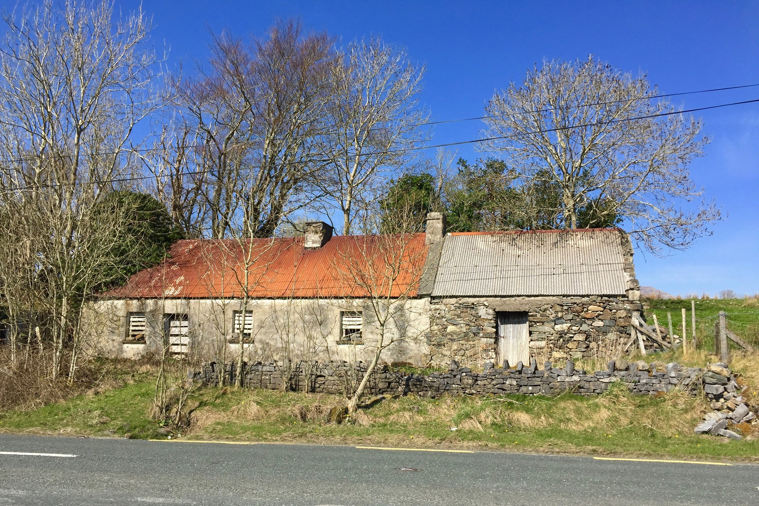 The road to Clifden is covered with rolling farmland and quaint stone cottages like this one.