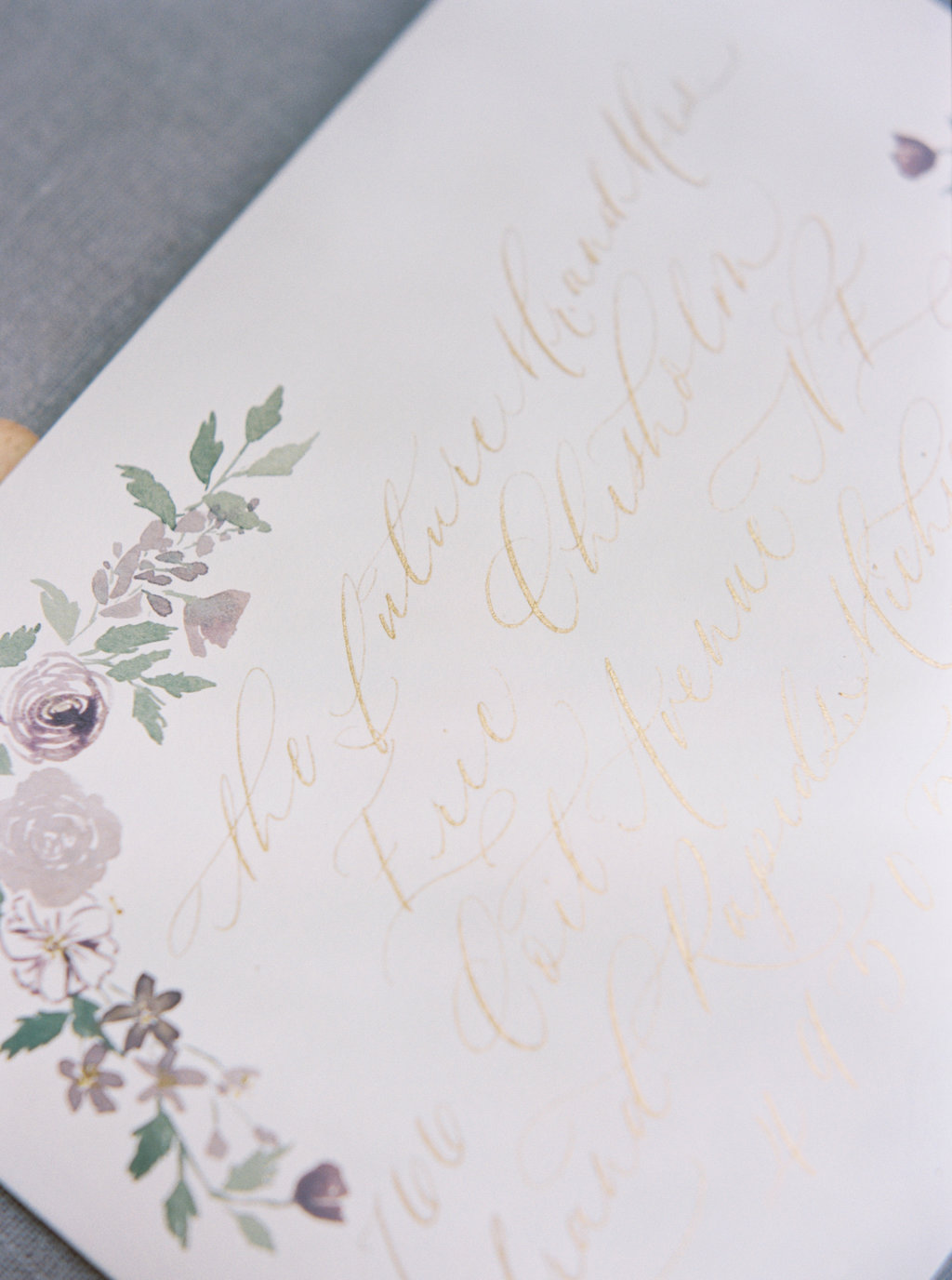 Gold calligraphy and watercolor flowers on wedding envelopes.