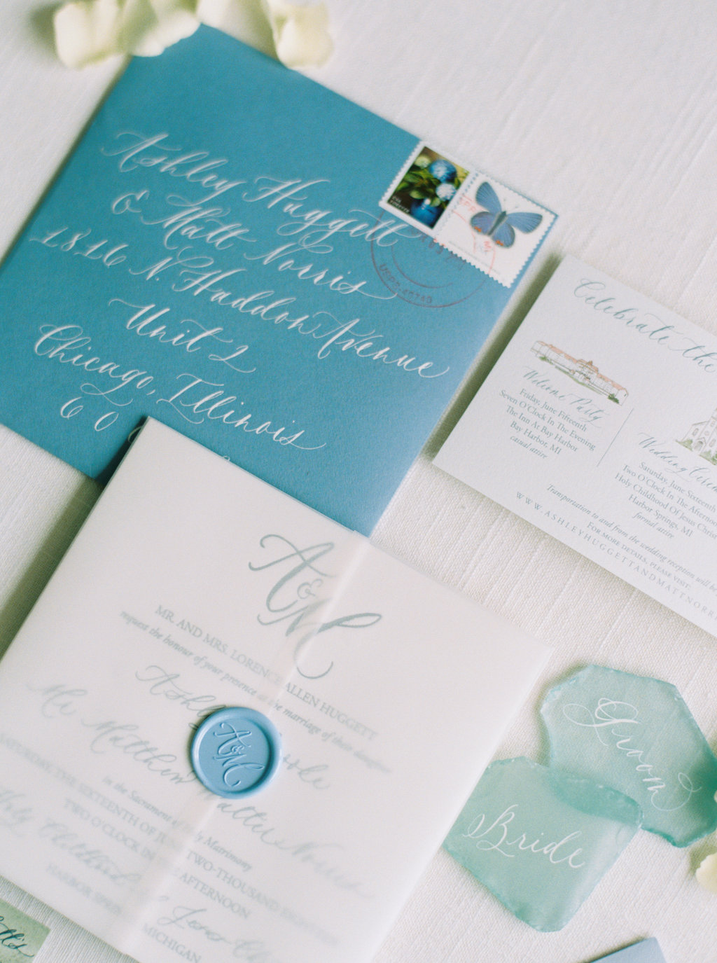 Blue envelopes with white calligraphy. Custom wax seal and beach glass escort cards.
