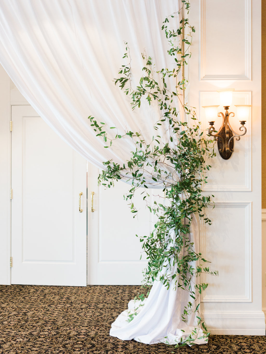 White curtain and greenery wedding decor for entryway.
