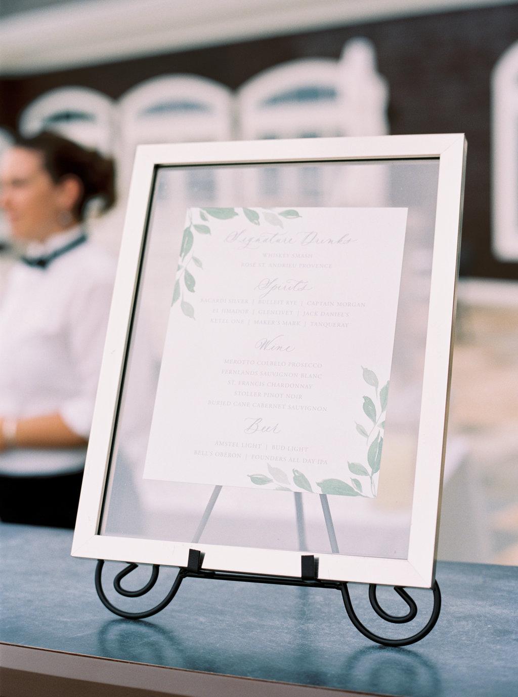 Custom watercolor bar menu in floating glass frame.