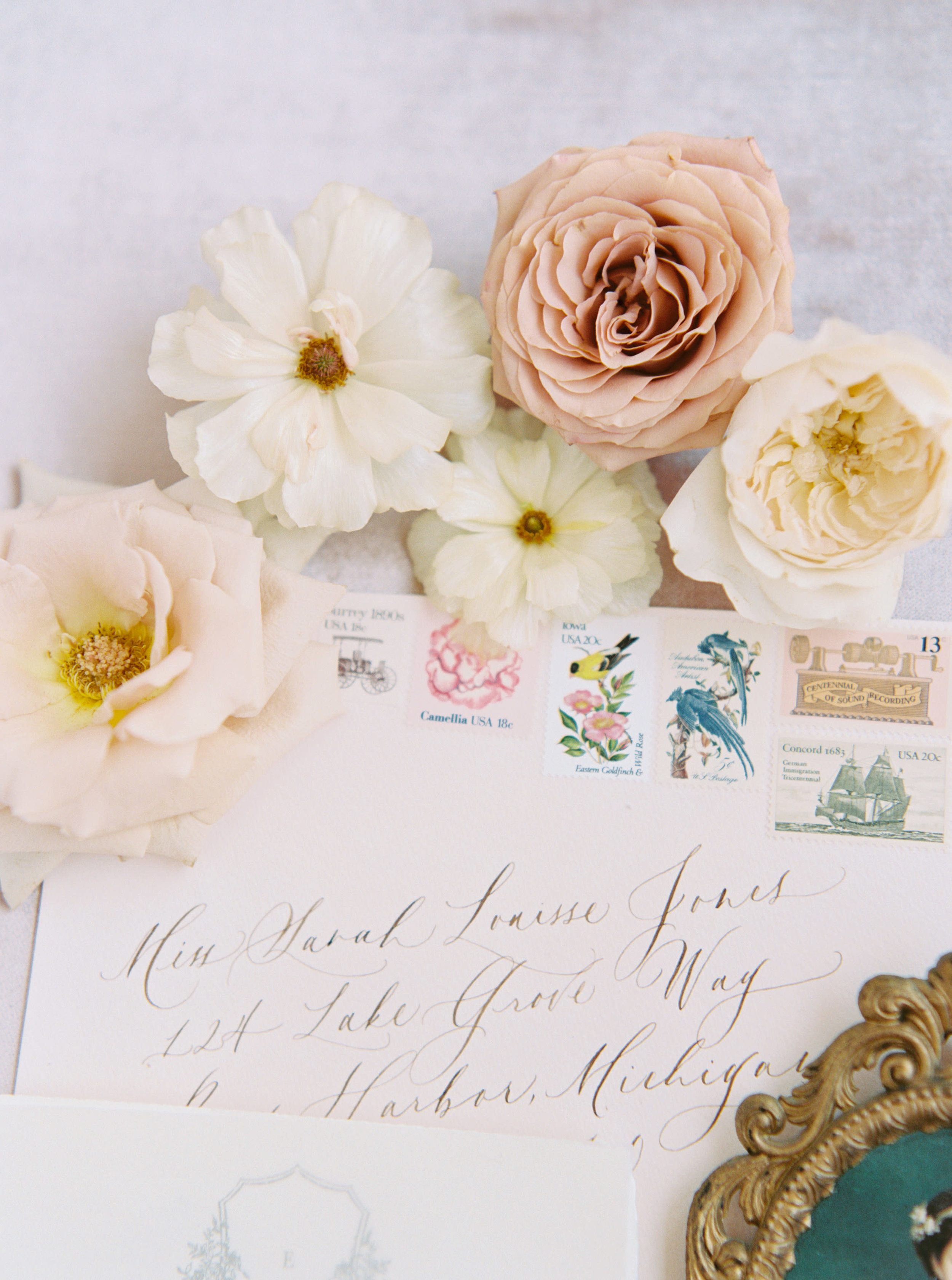 Gold calligraphy on blush envelopes with vintage stamps for classic and traditional wedding.