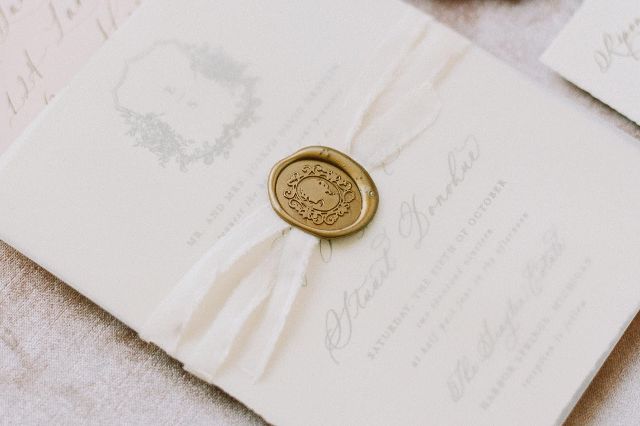 Classic wedding invitations with vellum overlay, silk ribbon and custom antique gold wax seals.