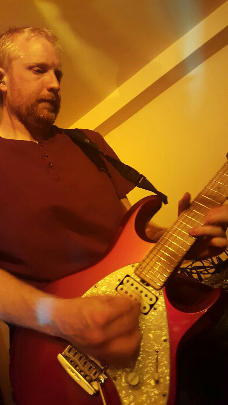 Charlie pulling a solo on his Musicman guitar