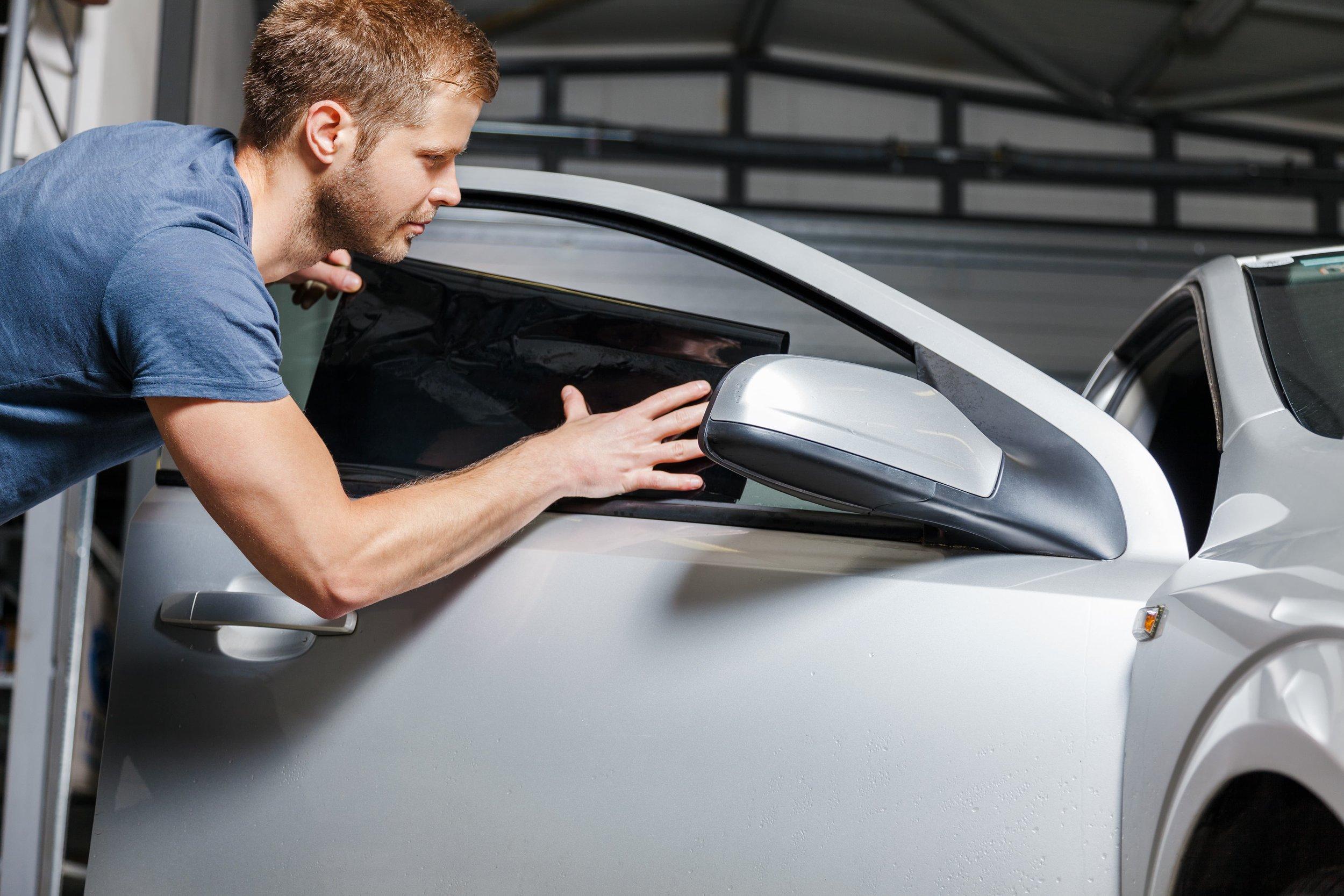 man-applying-window-tint-to-car