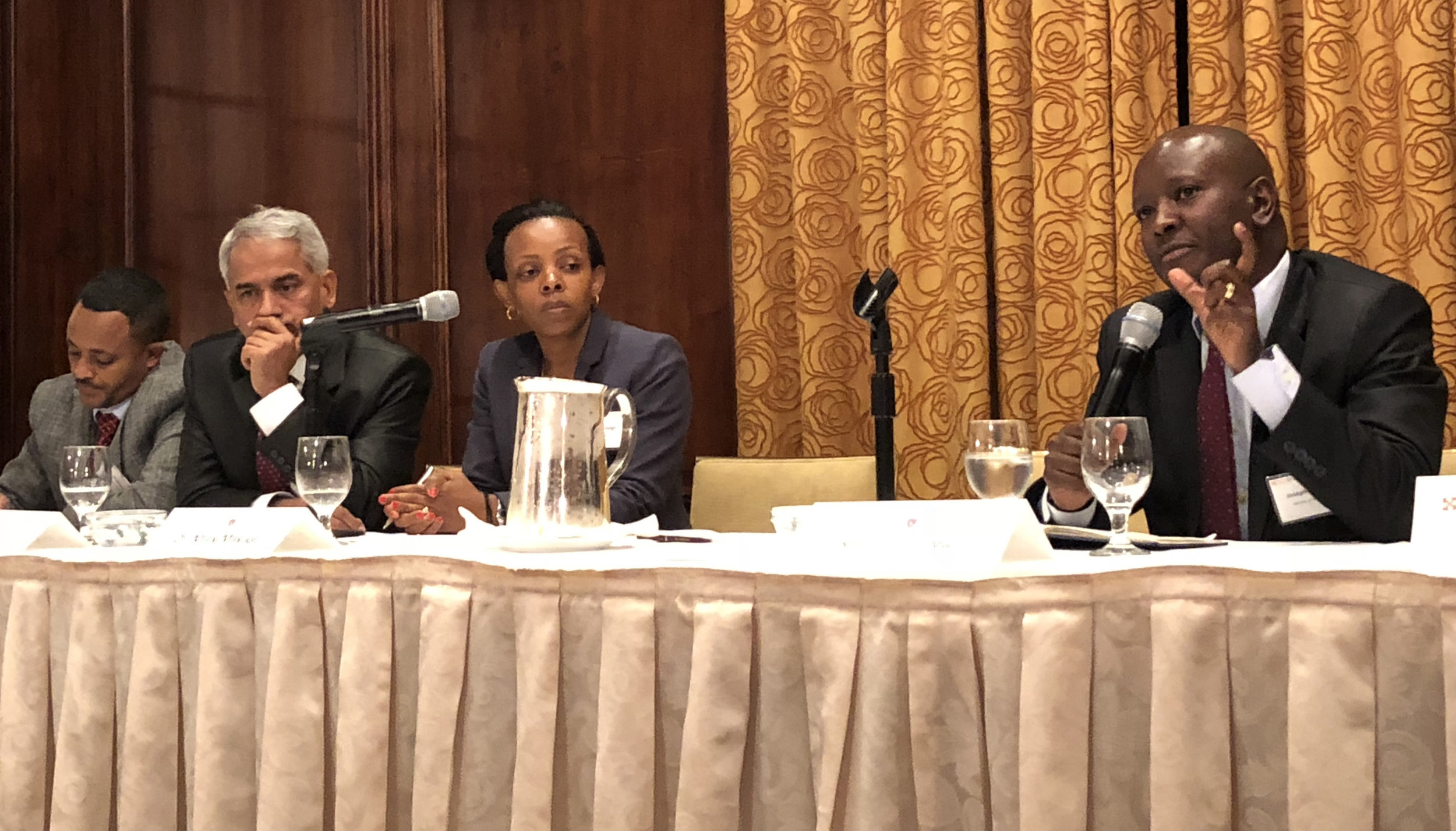 dr. joseph kibachio (right) speaks on a panel of national ncdi poverty commissioners alongside (from left to right) dr. wubaye walelgne, dr. baghawan koirala, and dr mary mayige.