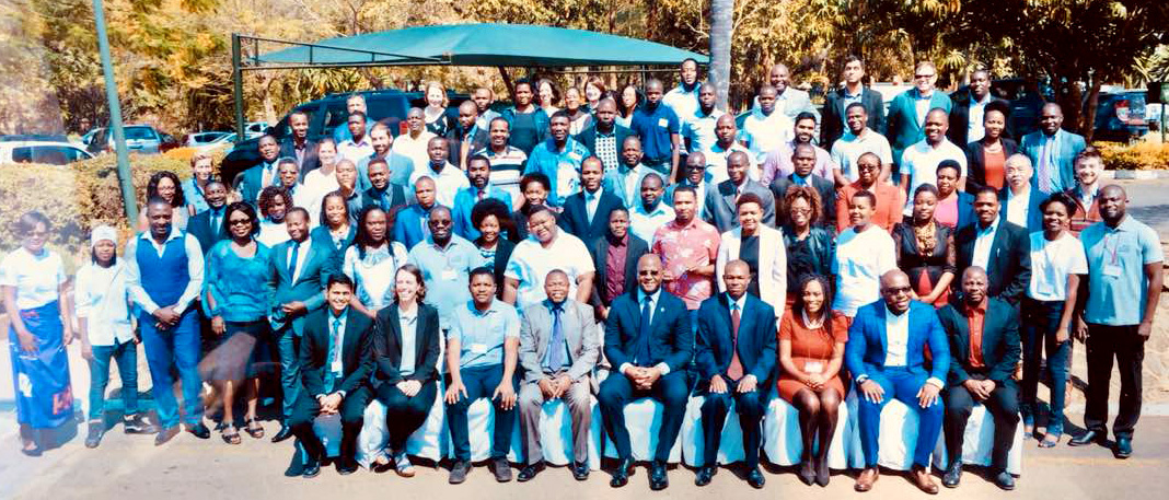 The honorable atupele muluzi (front row center with blue suit and tie) poses for a photo with members of the malawi ncdi poverty commission and other participants at the launch of the commission report.