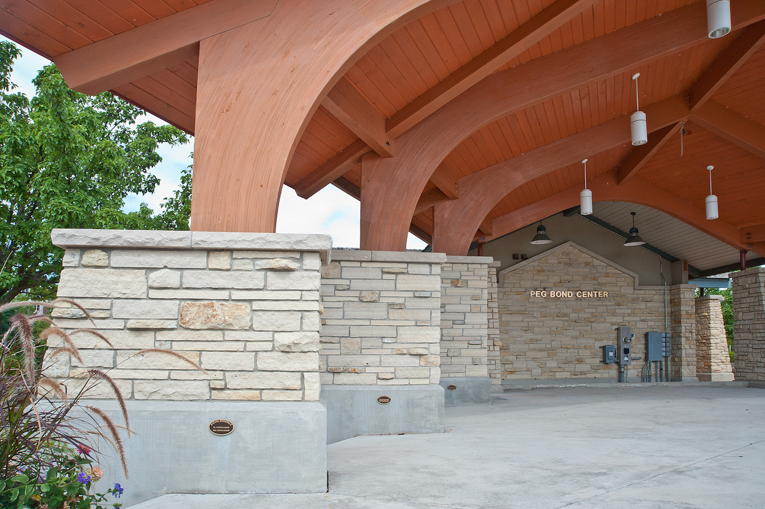 The curved timber beams and the stone piers that step down in size as they spread forward make the band shell appear larger.
