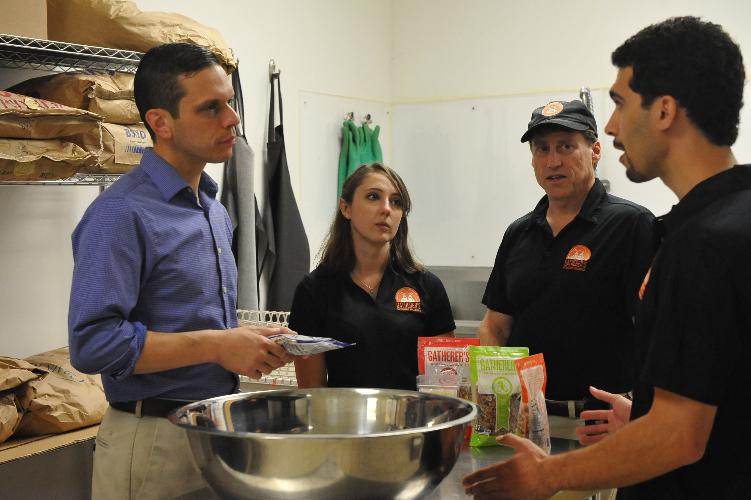Assemblyman Angelo Santabarbara talks with the owner of Gatherer's Granola and his staff about how he support their business.