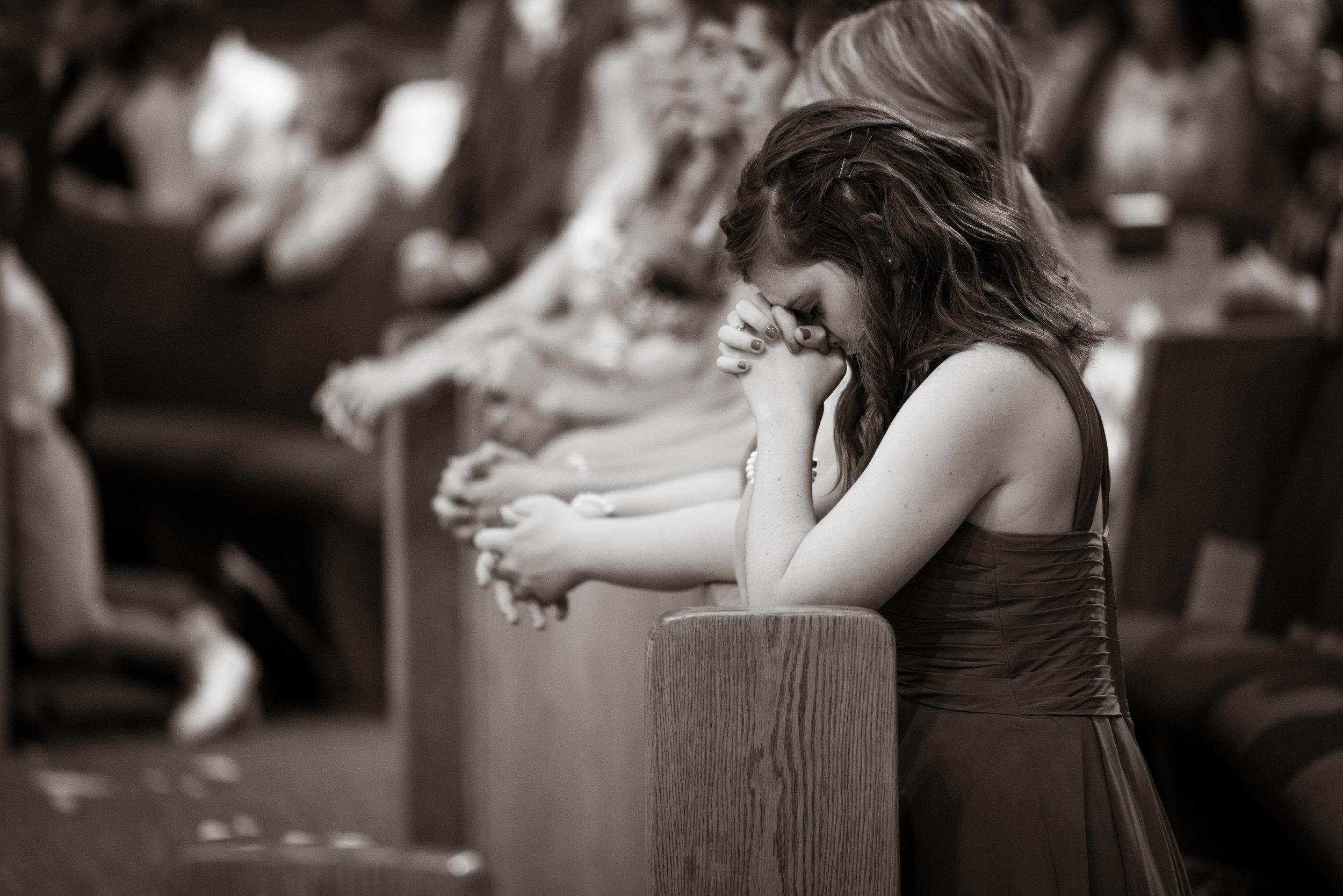 Bridesmaid praying during ceremony | St Mary Magdalene Catholic Church Simpsonville, SC