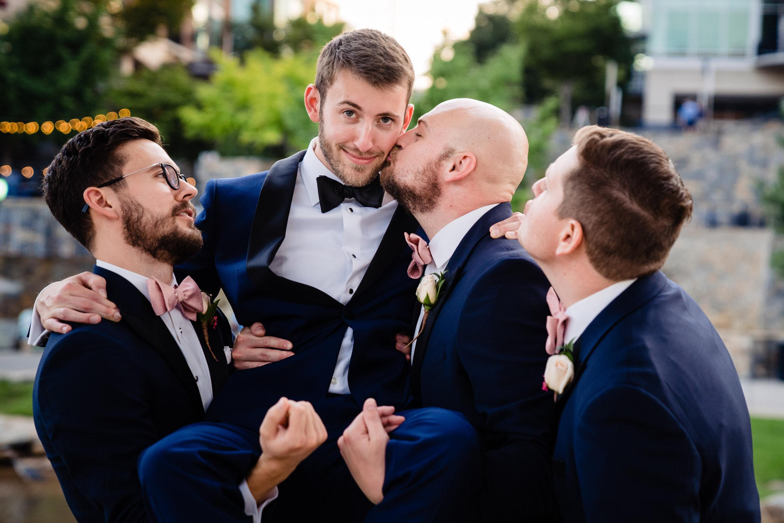 Groom getting kiss from Groomsman   Huguenot Mill Wedding Greenville SC