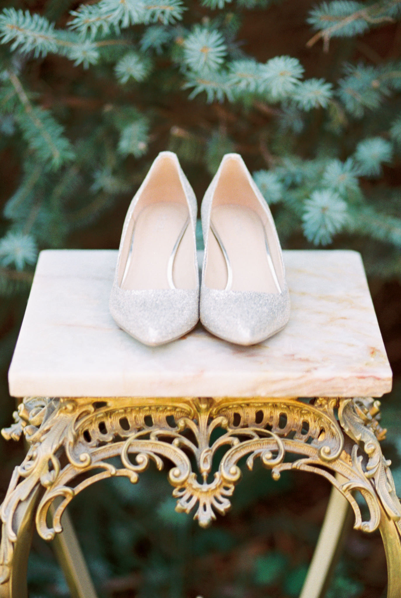 Michael Kors glitter wedding shoes sitting on marble and gold table