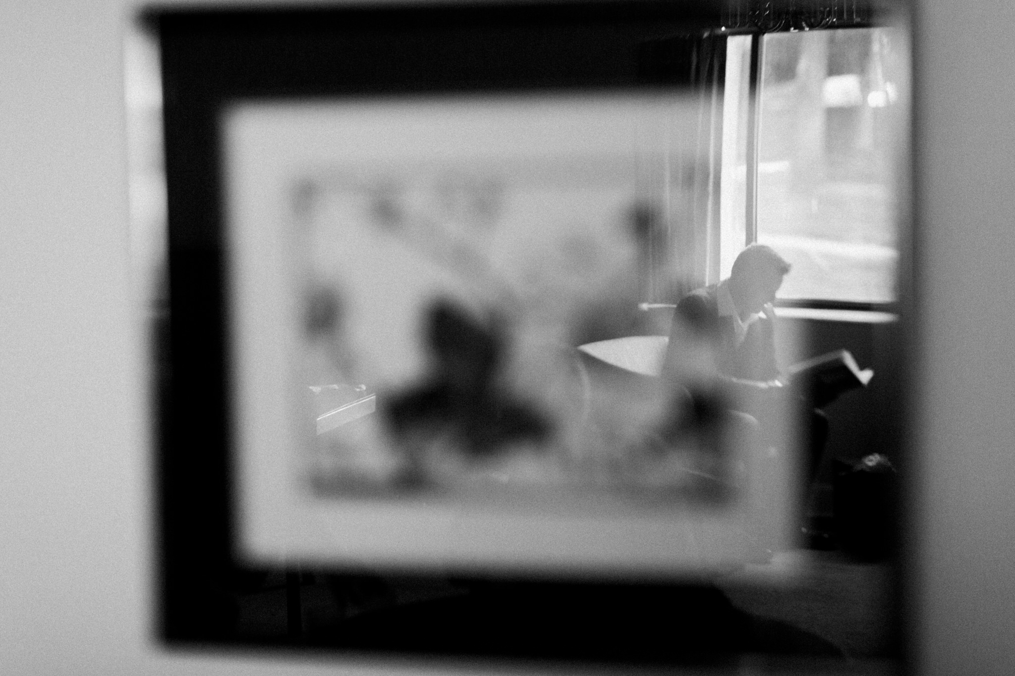 Reflection photo of groom reading his wedding gift from the bride. Reflection is in wall picture glass.