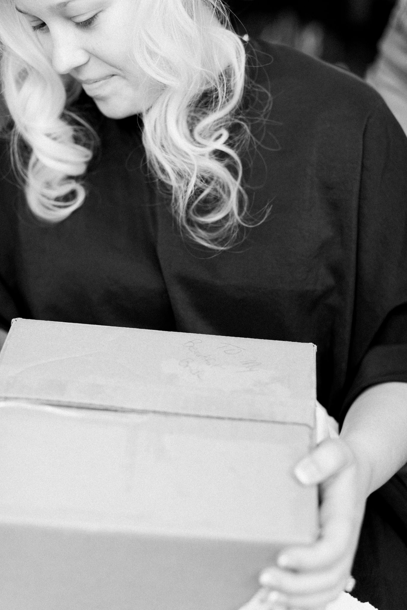Bride opens her gift box from the groom while getting ready for her Louisville wedding